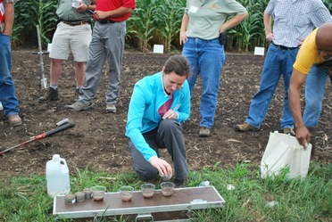 Dr. Meghan Buckley, assistant professor, College of Natural Resources, University of Wisconsin-Stevens Point, demonstrates aggregate stability from soil samples treated with FGD gypsum.